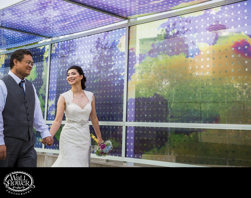Bride and groom walk by wall at Olympic Sculpture Park