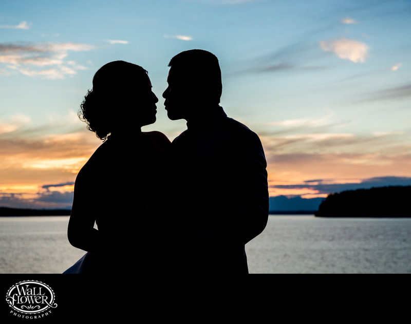 Silhouette of bride and groom by Puget Sound at sunset