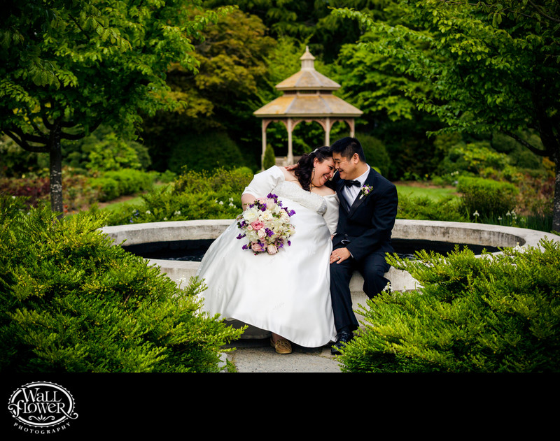 Bride and groom sitting in Woodland Park Rose Garden
