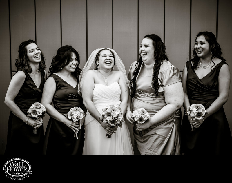 Bride, bridesmaids laugh by Puyallup City Hall building