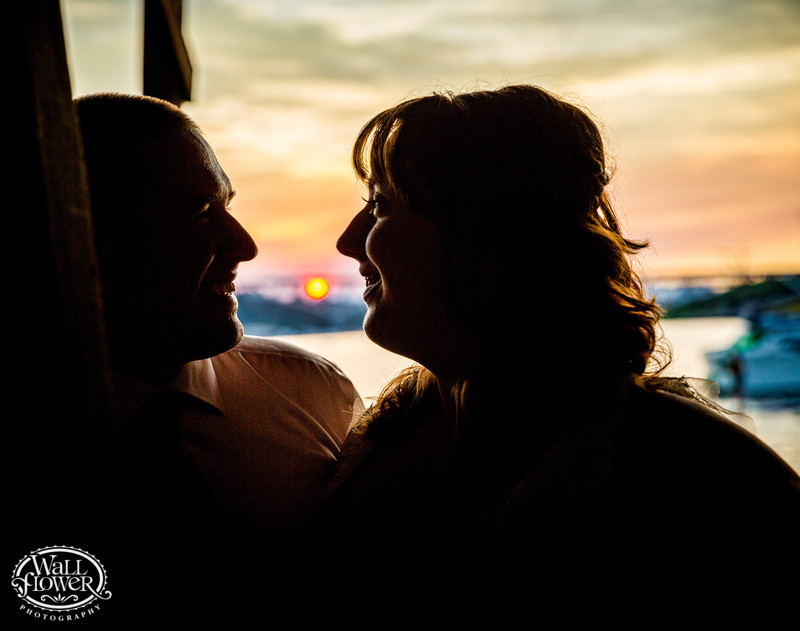 Bride and groom silhouette on Lake Union dock at sunset
