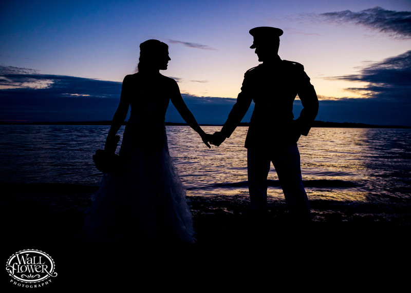 Silhouette of bride and military groom on beach at dusk