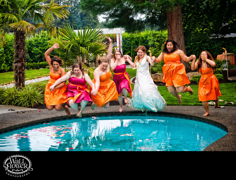 Bride and bridesmaids jump into swimming pool