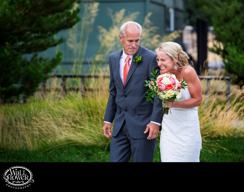 Bride grins at groom as her dad walks her to wedding