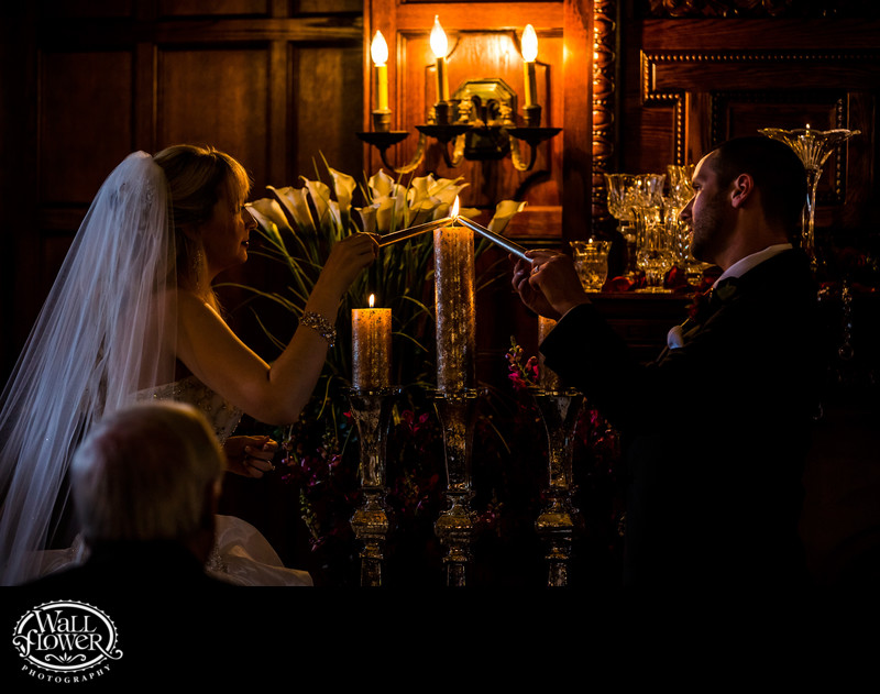 Bride and groom light unity candle in Thornewood Castle
