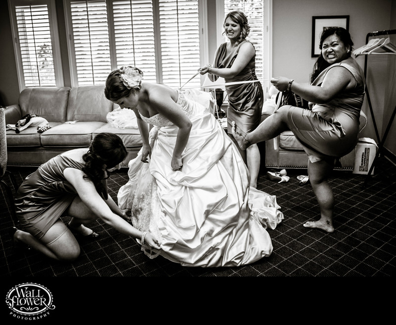 Bridesmaids use extra leverage to tighten bride's dress