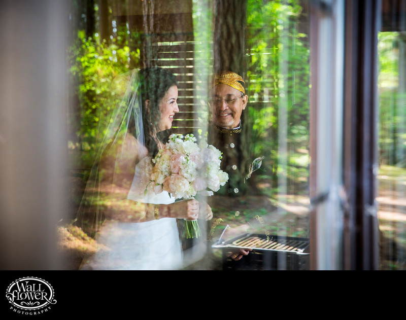 Indonesian bride and father seen in reflective window