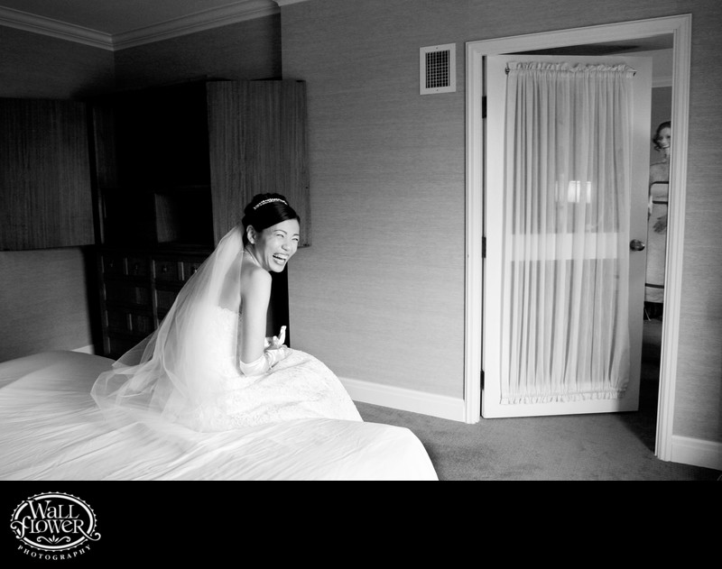 Bride on bed laughs from bridesmaid peeking into room