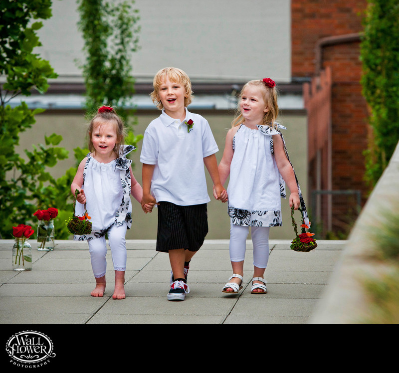 Cute wedding kids hold hands while approaching ceremony