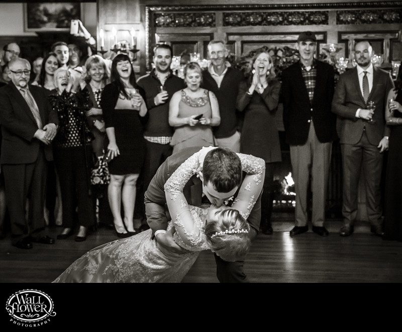 Groom dips and kisses bride at end of first dance in Thornewood Castle's Great Hall
