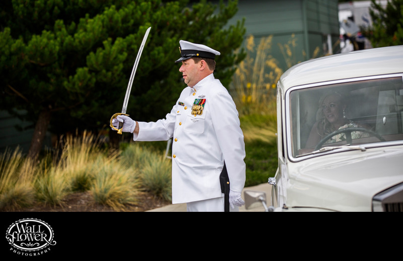 Bride's Navy officer father salutes with sword as bride watches from Bentley