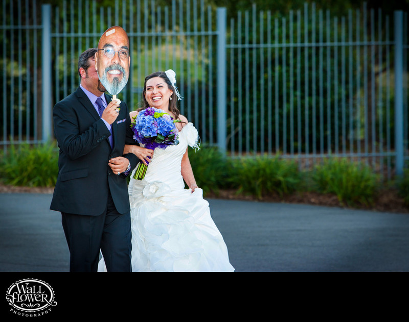 Bride's brother holds mask of absent father's face while escorting bride to wedding ceremony at PDZA