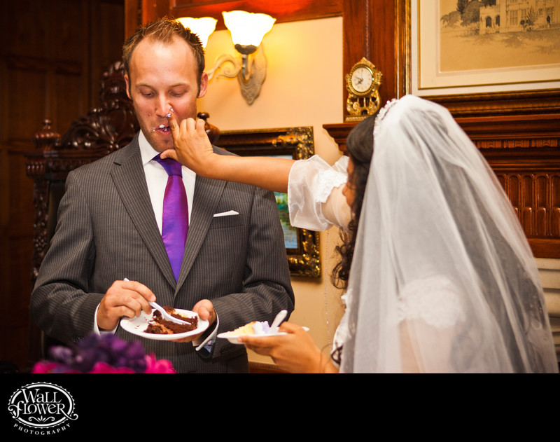 Bride shoves frosting-coated finger up groom's nose
