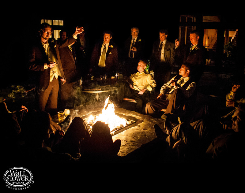 Groom gives toast to friends around fire at night