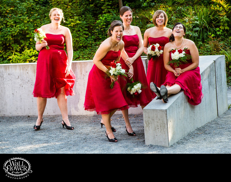 Bridesmaids in red dresses laugh during photo shoot