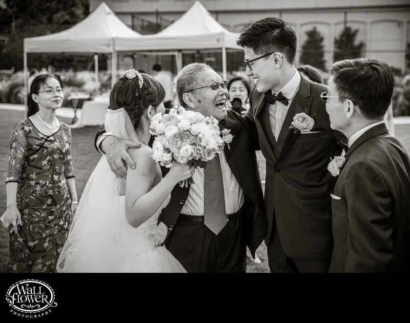 Bride's grandpa joyously hugs newlyweds after wedding