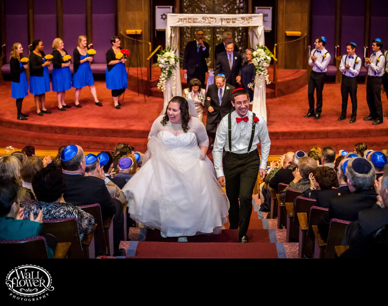 Jewish bride and groom grin while departing ceremony