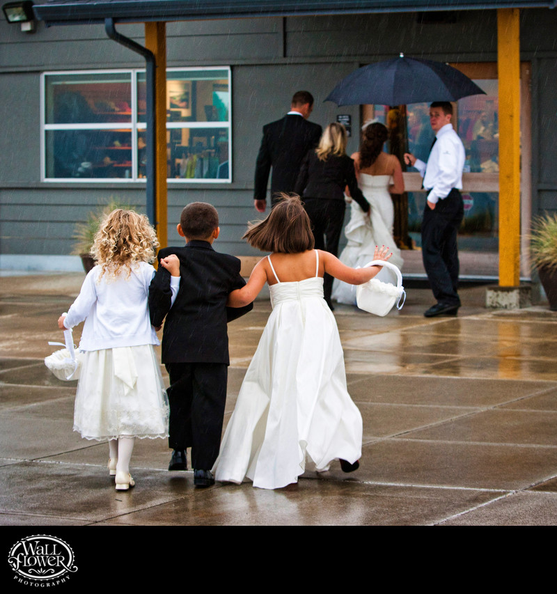 Ring bearer, flower girls hurry through rainy courtyard
