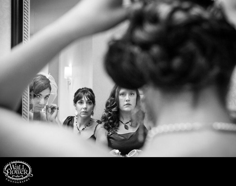 Bride and bridesmaids adjusting birdcage veil in mirror