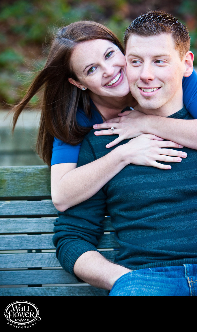 Engagement portrait of woman hugging man from behind