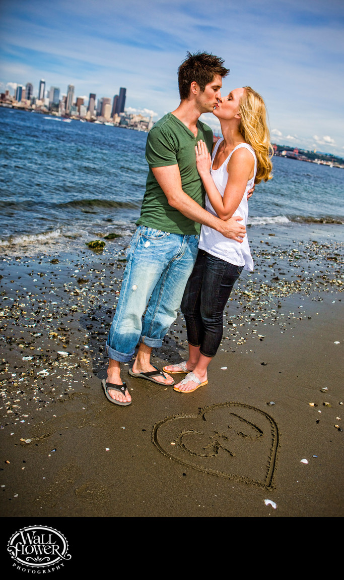 Engagement portrait kiss on Alki Beach, Seattle behind