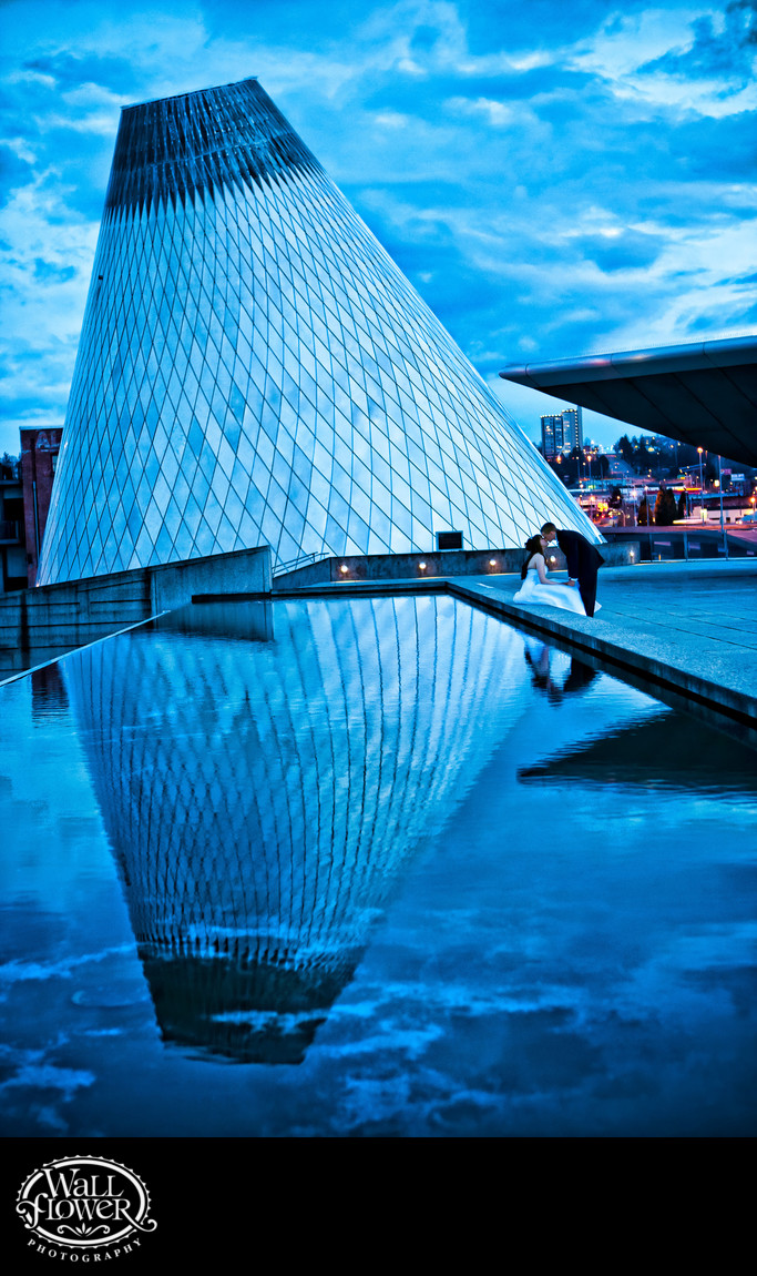 Bride and groom kiss by Museum of Glass cone at dusk