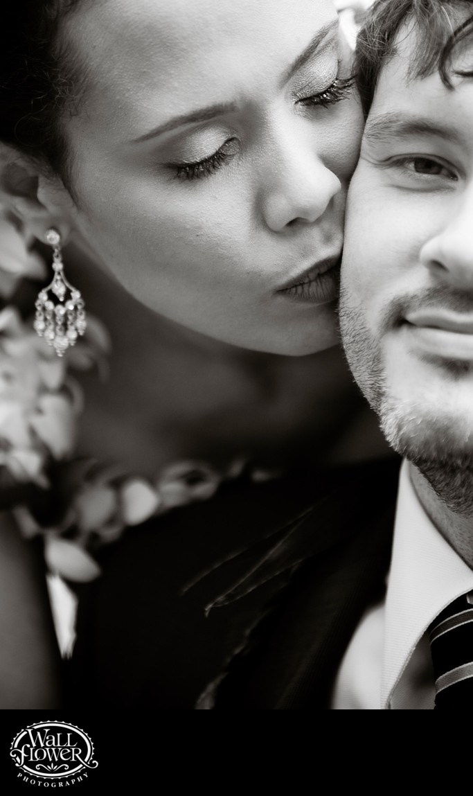Groom kissed on cheek by bride with creative framing
