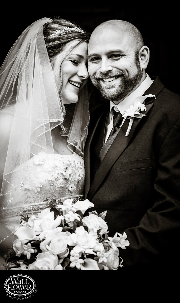 Bride and groom nuzzle in black and white photo