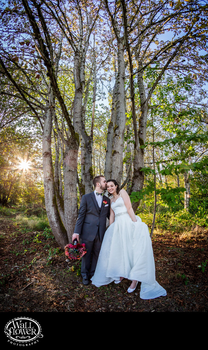 Bride and groom pose by tree near sunset