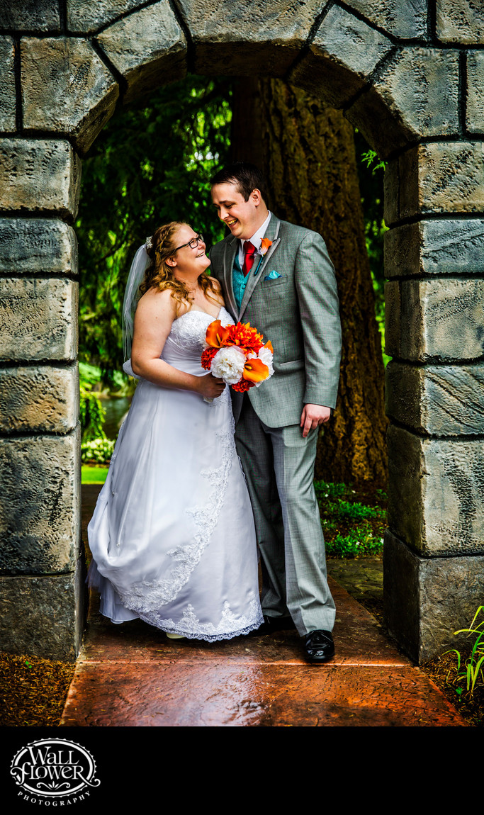 Bride and groom in stone archway at Rock Creek Gardens