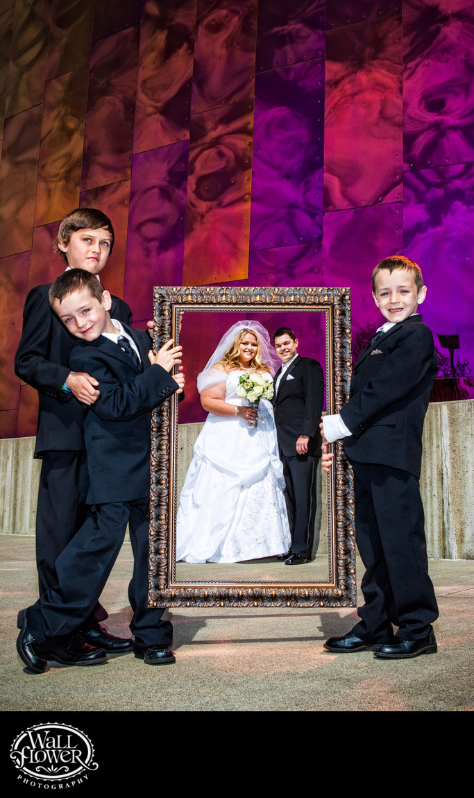 Bride and groom in picture frame held by ring bearers