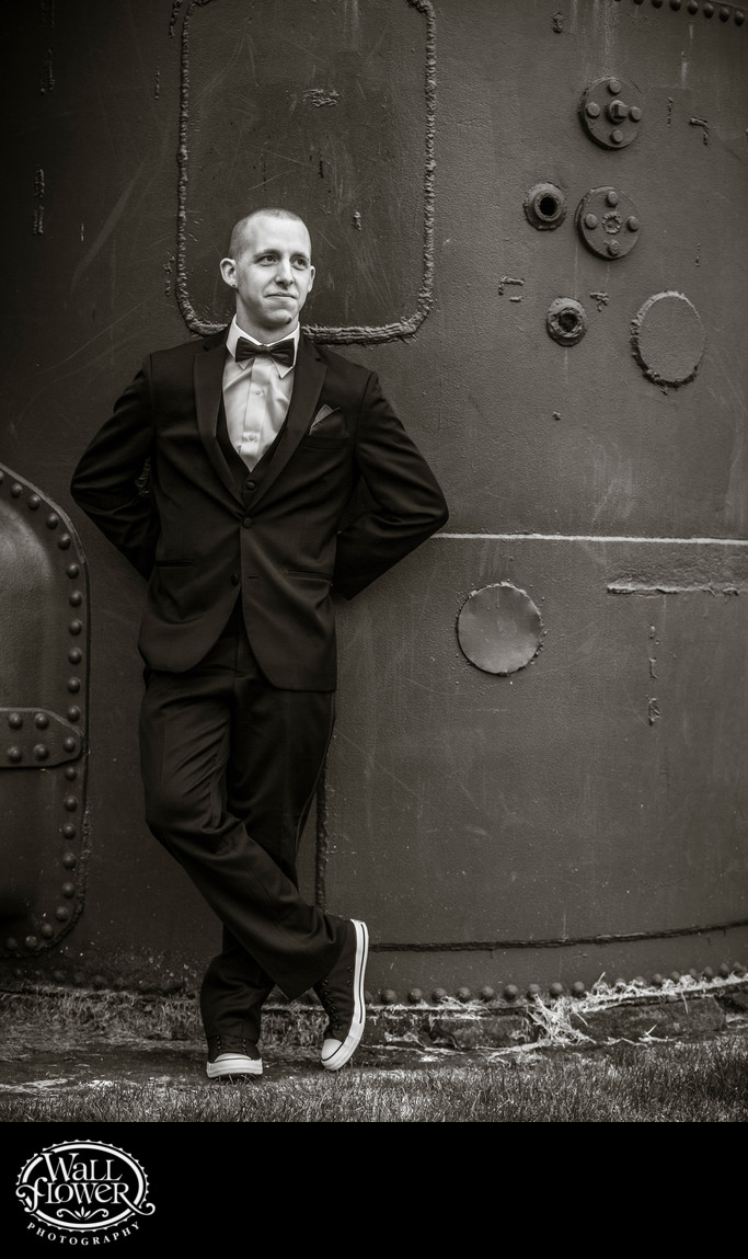 Groom leans against metal at Seattle's Gas Works Park