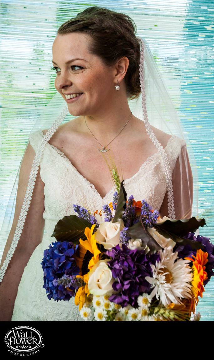 Bride smiles in front of glass wall at Hotel Murano