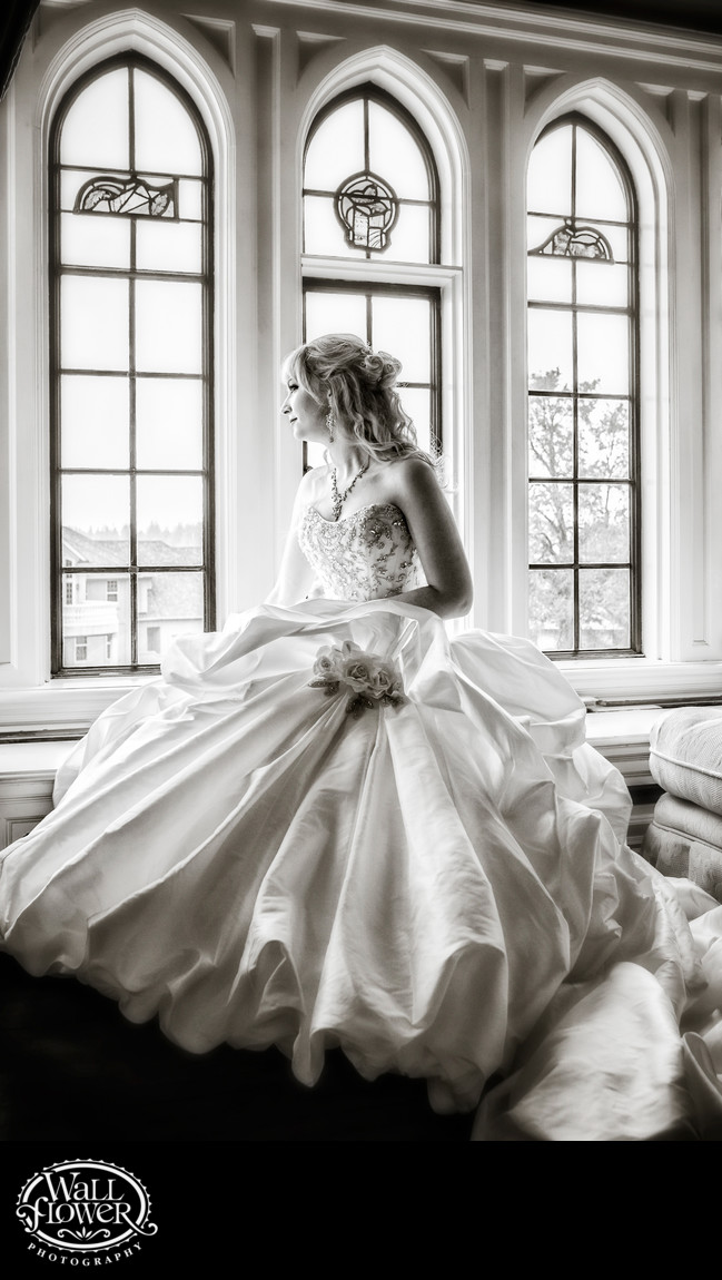Bride looks out windows in Thornewood Castle suite