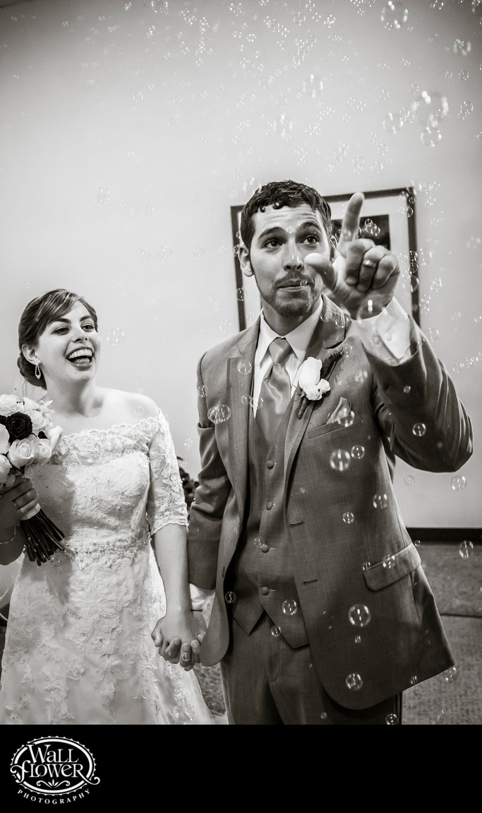 Groom pokes bubbles with finger as bride laughs