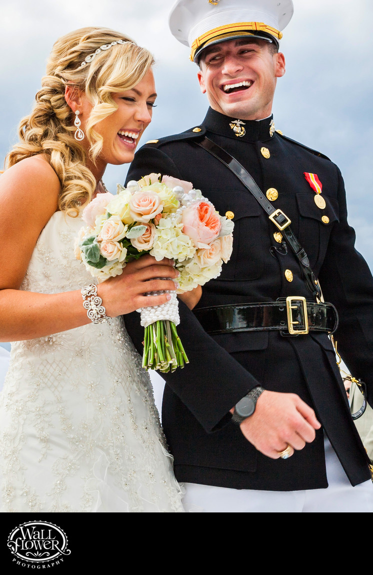 Bride and military groom laugh at end of wedding