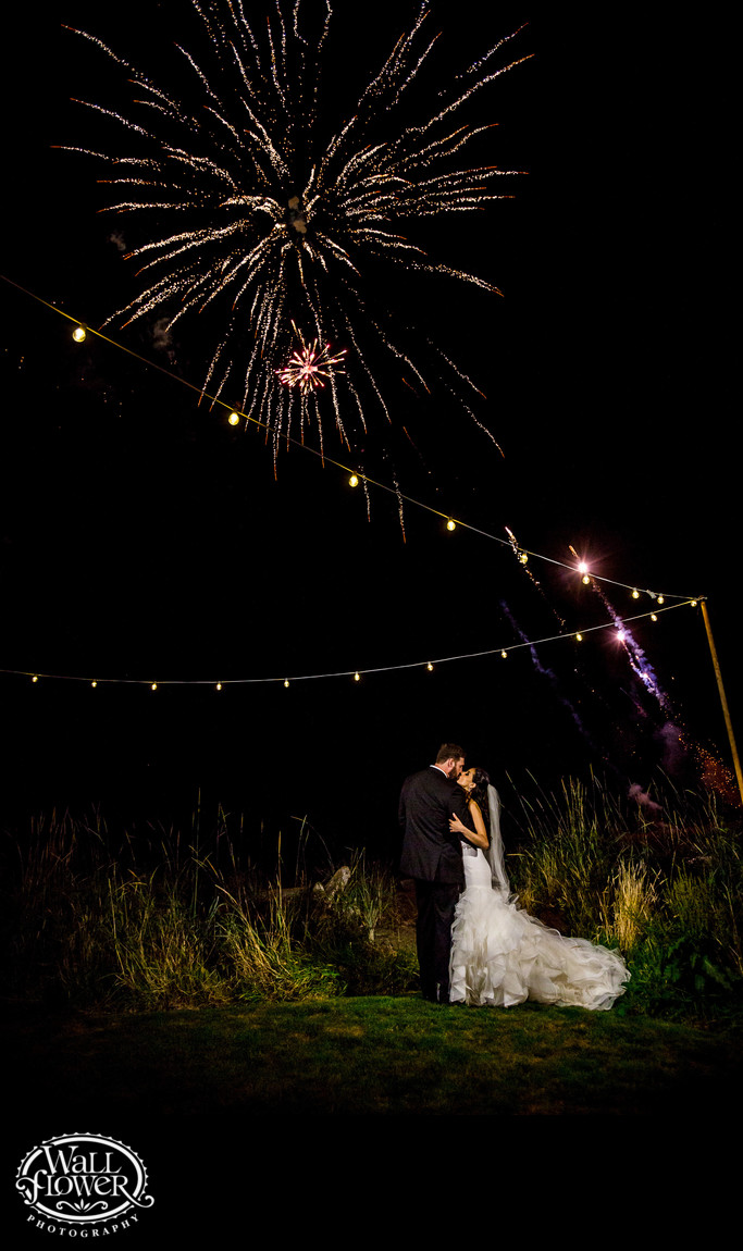 Bride and groom kiss under fireworks at Edgewater House