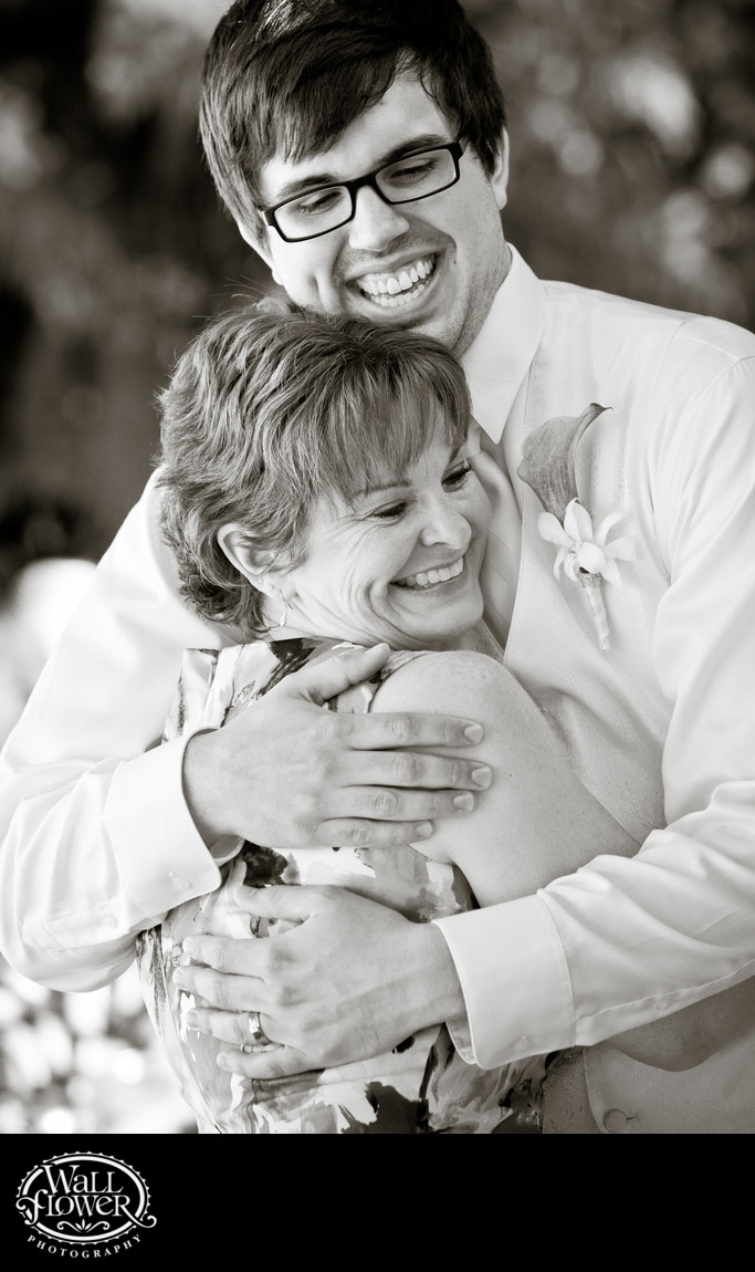 Groom hugs mother of bride during wedding reception