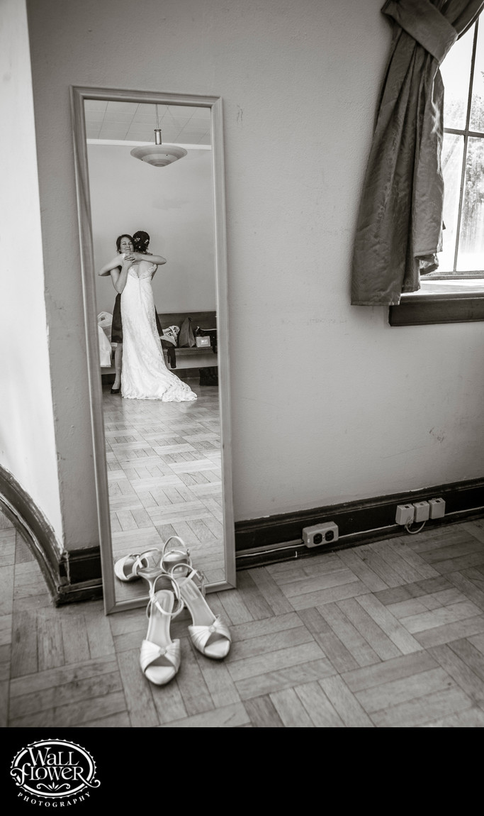 Reflection of bride hugging bridesmaid, with shoes