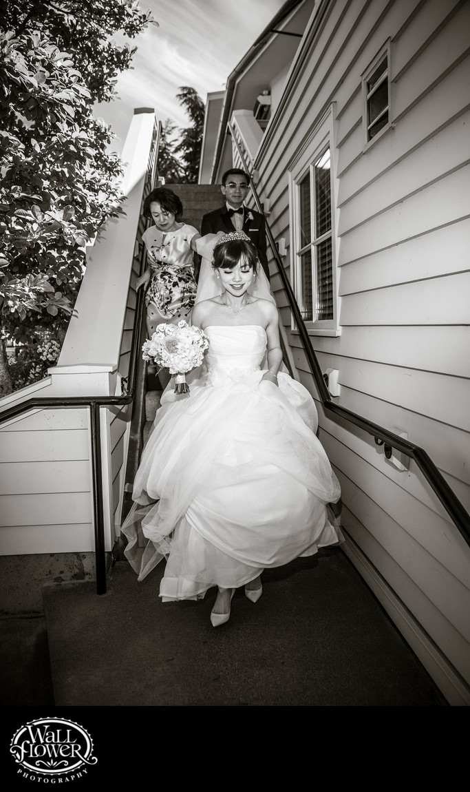 Bride's parents carry her dress while descending stairs