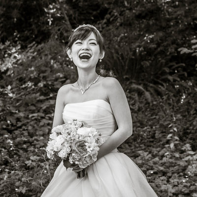 Bride laughs during wedding photo shoot in forest