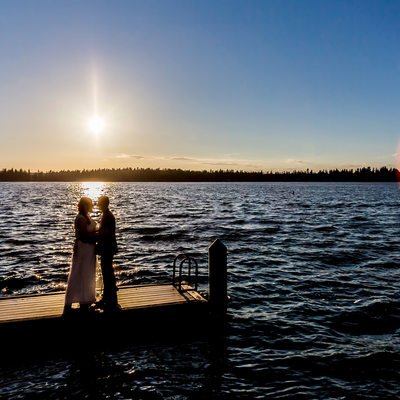 Bride and groom sunset kiss on Thornewood Castle dock