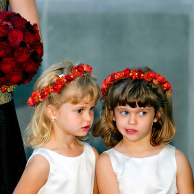 Twin flower girls whisper as bride approaches