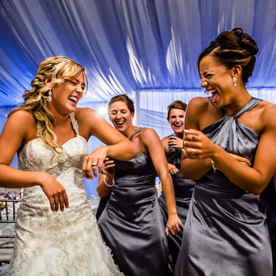 Bride and bridesmaids laugh while dancing in reception
