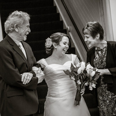 Bride and parents laugh as they escort her down aisle