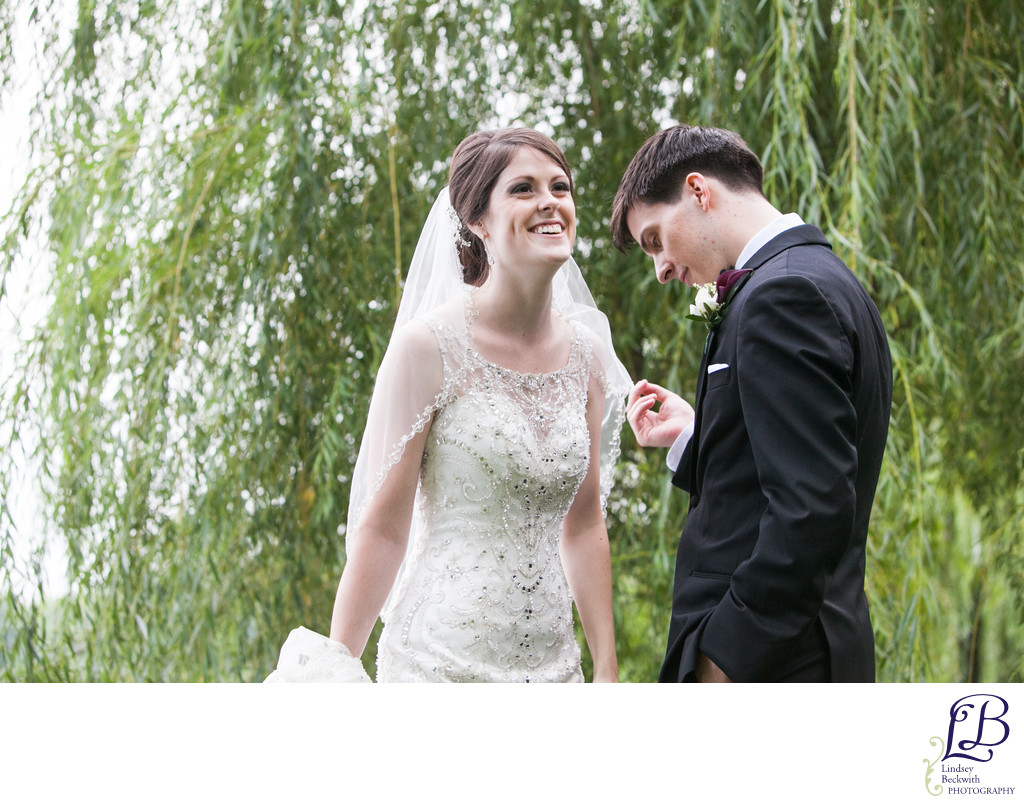 Bride in lace dress and groom laughing willow tree