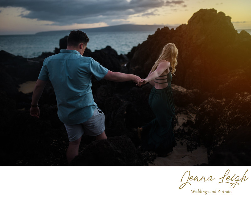 Couple climbing beach rocks in Maui, Hawaii