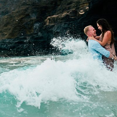 Ocean waves washing over happy embraced couple
