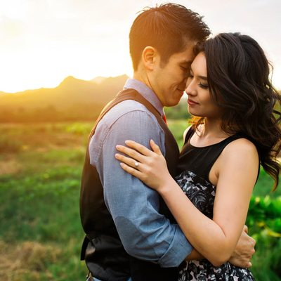 Couple embracing in front of a sunlit mountain.