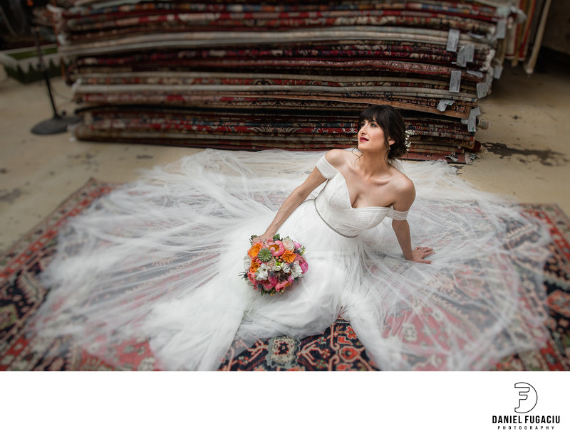 Bride holding bouquet posing on persian rug.